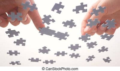 Puzzle pieces and hands of closeup. Task and subtask concept. Pastime, a hobby. Teamwork concept. Completing the task. Business solution concept. Full understanding of final product. Learning concept