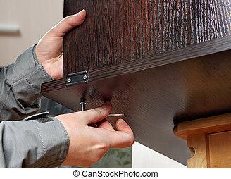 Allen furniture key in hand, fastens screw, close-up. -...