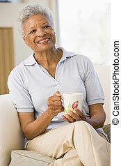 assento mulher, em, sala de estar, com, café, sorrindo