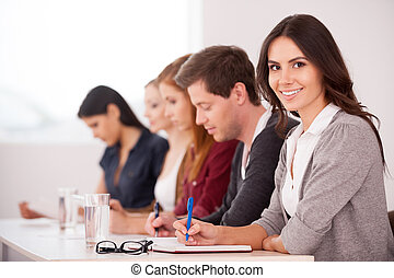 assento mulher, pessoas, jovem, junto, seminar., enquanto, câmera, atraente, outro, tabela, sorrindo