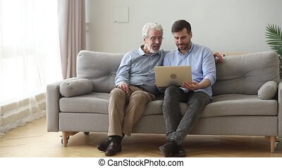 asseoir, ordinateur portable, père, fils, embrasser, utilisation, personne agee, divan, heureux