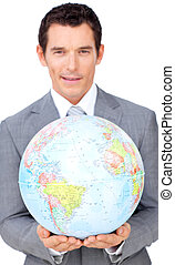 Assertive businessman holding a terrestrial globe isolated...