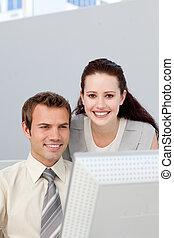 Assertive businesswoman helping her colleague