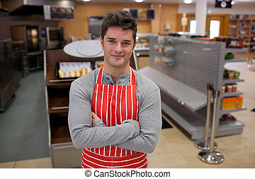 Assertive cook smiling at the camera in front of his bakery