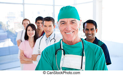 Assertive senior surgeon standing with his colleagues in a...