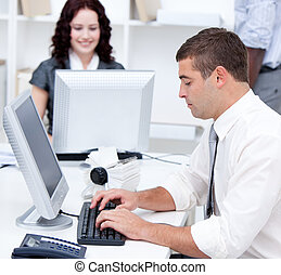 Assertive young business people working at computers in the...