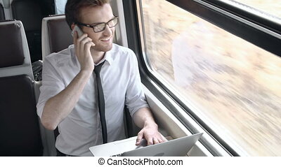 Train passenger multitasking computing and talking on the phone