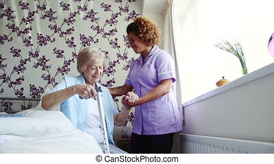 Home caregiver assisting a senior woman as she gets up from sitting on the bed.