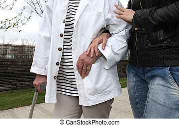 Assistant helping an elderly person walk