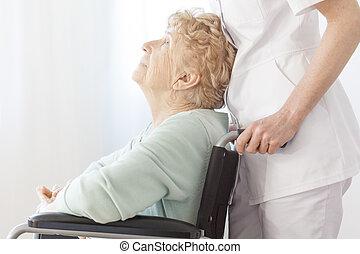 Assistant helps elderly woman