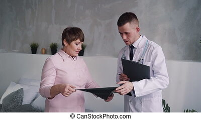 Assistant of doctor discuss x-ray and signed document with...