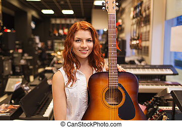 assistant or customer with guitar at music store