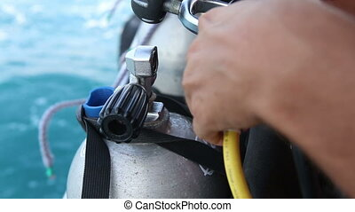 assistant puts on oxygen tube to oxigen cylinder for diving