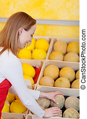 Assistant repacking melons in a display