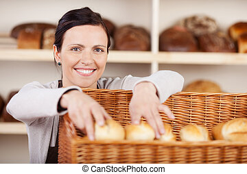 Assistant selecting rolls in a bakery - Smiling attractive...