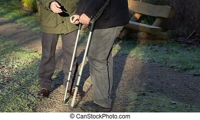 Assistant try to help disabled man on crutches