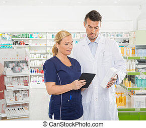 Assistant Using Digital Tablet While Pharmacist Holding ...