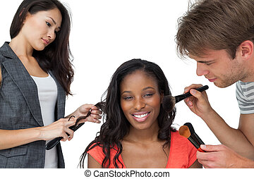 Assistants applying make-up to a female model