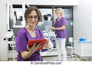 assistent, gebrauchend, digital tablette, während, kollege, arbeiten, dentis