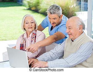 assistere, custode, coppia, usando, maschio maggiore, laptop