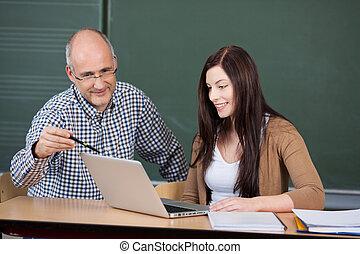 assisting, женщина, профессор, против, классной доски, с помощью, портативный компьютер