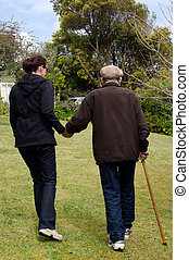 Young woman helping and supporting her grandfather to walk outdoor in the garden with his support walking stick.