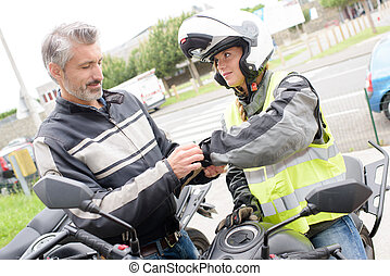 assisting in putting a motorcycle gloves