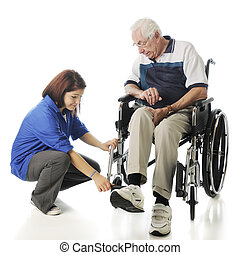 An attractive young teen adjusting the foot pedals on an elderly man's wheel chair. On a white background.