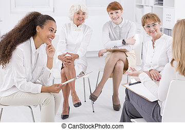 Association of white dressed women sitting together in circle