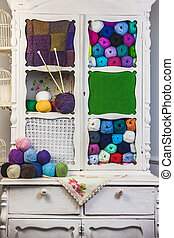 Assorted balls of natural colored yarn in a vintage case