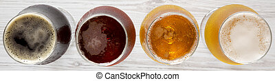Assorted beers on a white wooden surface, top view. Overhead, from above.