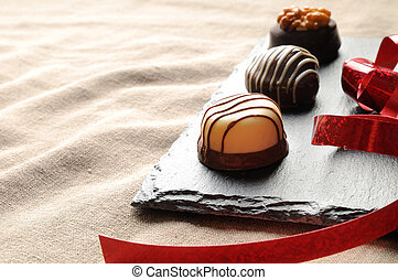 Assorted bonbons on a slate plate with red ribbon close up