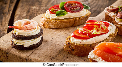 Assorted canapes on bread and blinis