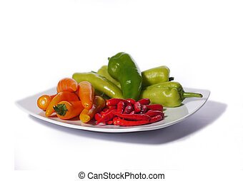 Assorted chili peppers on a white plate, isolated