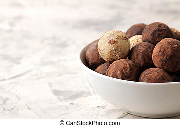 assorted chocolates. Candy balls of different types of chocolate on a light concrete background. free space