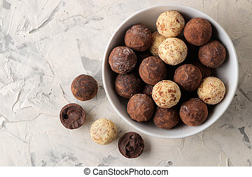 assorted chocolates. Candy balls of different types of chocolate on a light concrete background. top view