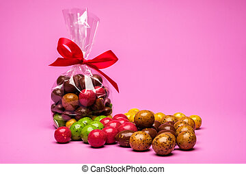 Assorted chocolates on a pink background. Packing with sweets