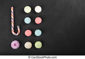 Assorted colorful french macarons and christmas lollipop on a black background. Space for text, closeup, top view