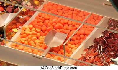 Assorted colorful jelly candies on counter at a food market...