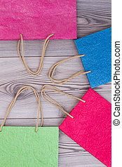 Assorted colors gift bags on wooden background.
