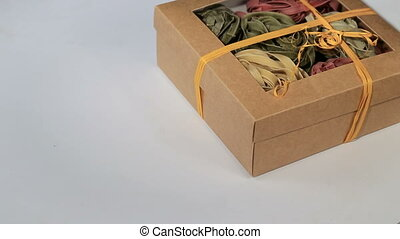 Assorted different kinds of pasta in a paper box turns on a white background