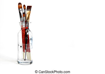 Assorted dirty old painting brushes in a glass flask....