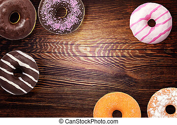 Assorted donuts on wooden background
