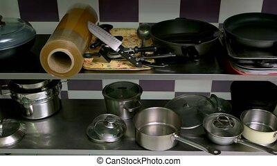 Assorted essential kitchen utensils. Stainless steel pans,...
