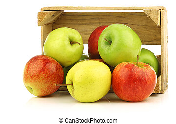 assorted fresh apples in a wooden crate on a white ...