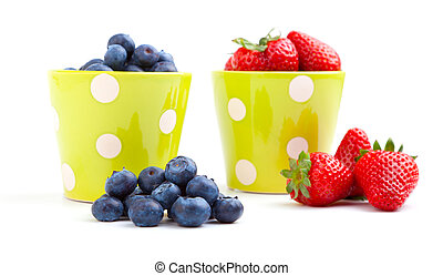 Assorted fresh picked berries in a green mug over a white background. Vertical format with reflection.