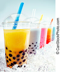 Assorted Fruity Boba Tea Cocktails in a row on crushed ice