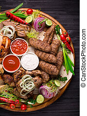 Assorted grilled meat and vegetables on rustic table
