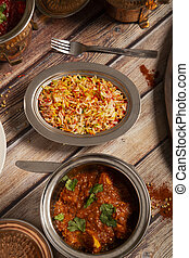 Assorted Indian dishes of rice and curry on wooden background. Top view. Vertical picture