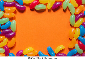 Assorted Jelly Beans border with copyspace on orange background.